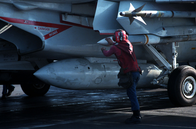 An ordnance crew member checks an AIM-7 Sparrow missile and an AIM-9 Sidewinder missile attached to a Fighter Squadron 142 (VF-142) F-14A Tomcat aircraft prior to the plane's launch from the flight deck of the nuclear-powered aircraft carrier USS DWIGHT D. EISENHOWER (CVN 69)