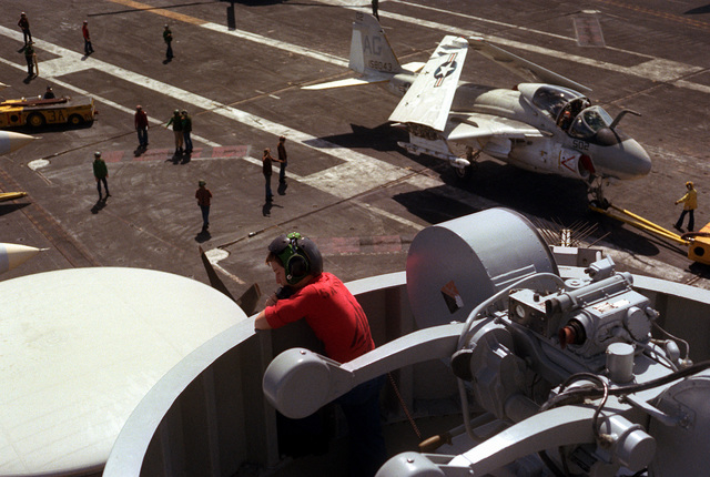 As seen from the ship's O-9 level, an Attack Squadron 65 (VA-65) A-6E Intruder aircraft is moved clear of the arresting wires on the flight deck of the nuclear-powered aircraft carrier USS DWIGHT D. EISENHOWER (CVN-69)