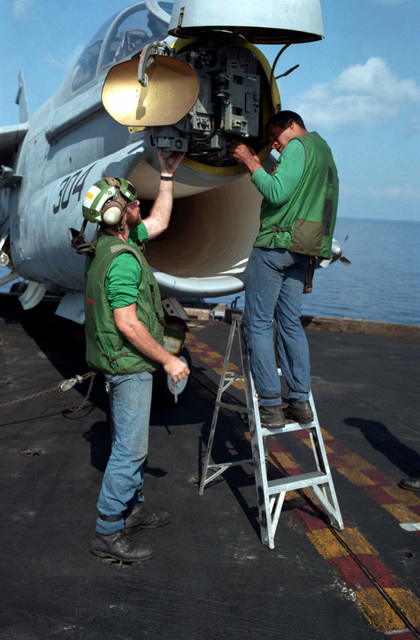 Maintenance crew members of Attack Squadron 66 (VA-66) service the APQ-126 radar unit of one of their squadon's A-7E Corsair II aircraft aboard the nuclear-powered aircraft carrier USS DWIGHT D. EISENHOWER (CVN 69)