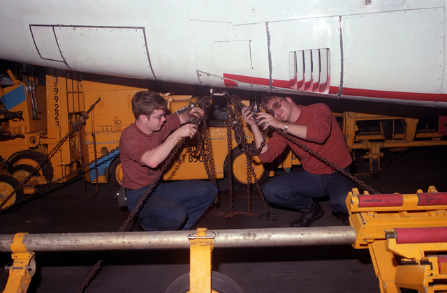 Maintenance crew members secure tie-down chains on an S-3A Viking aircraft aboard the nuclear-powered aircraft carrier USS DWIGHT D. EISENHOWER (CVN 69)