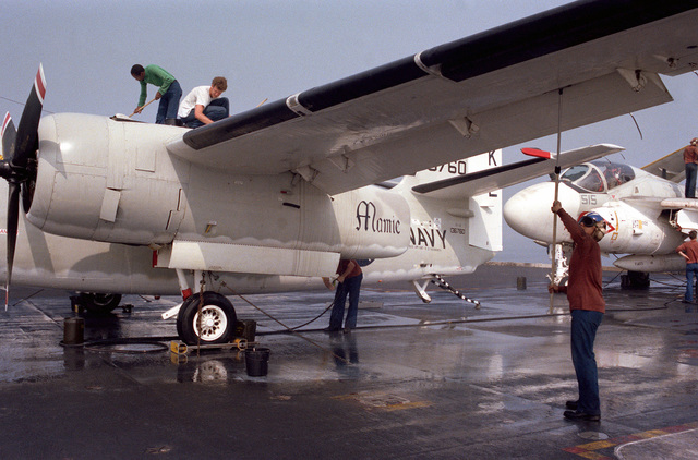 """Maintenance personnel wash down the ship's C-1A Trader carrier on-board delivery (COD) aircraft on the flight deck of the nuclear-powered aircraft carrier USS DWIGHT D. EISENHOWER (CVN 69). The aircraft has been named """"Mamie,"""" after Mamie Eisenhower, who personally christened the aircraft when she was aboard for the ship's commissioning in 1977"""