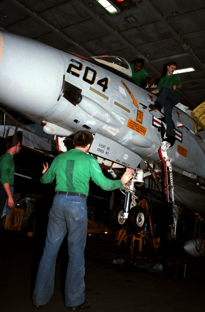 Maintenance personnel work on a Fighter Squadron 142 (VF-142) F-14A Tomcat aircraft in the hangar bay aboard the nuclear-powered aircraft carrier USS DWIGHT D. EISENHOWER (CVN 69)