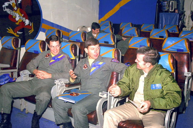 Pilots of Attack Squadron 66 (VA-66) converse before a briefing in the ready room aboard the nuclear-powered carrier USS DWIGHT D. EISENHOWER (CVN-69). The squadron insignia is on the wall