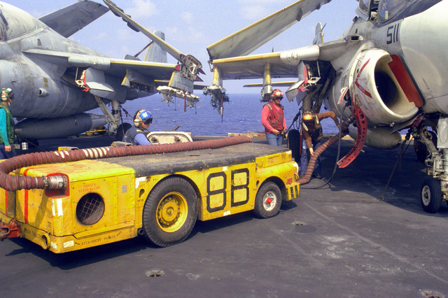 Sailors use an air hose from an MD-3A tow tractor to turn over the engines of an Attack Squadron 65 (VA-65) A-6E Intruder aircraft on the flight deck of the nuclear-powered aircraft carrier USS DWIGHT D. EISENHOWER (CVN-69)