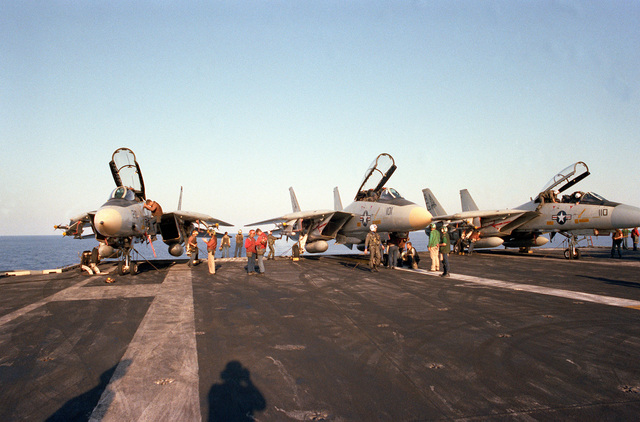 Three F-14A Tomcat aircraft are given preflight inspections while parked near the stern of the nuclear-powered aircraft carrier USS DWIGHT D. EISENHOWER (CVN 69). The two aircraft at right are from Fighter Squadron 143 (VF-143) and the aircraft at left is from Fighter Squadron 142 (VF-142)