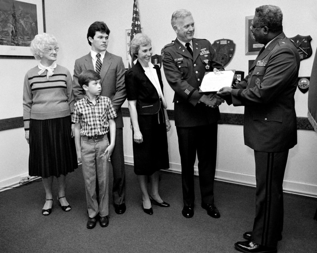 The Legion of Merit is presented to COL Robert E. Joiner III by BGEN Edward Honor, director of Resources the Management. Attending the ceremony at the Pentagon is from, left to right: COL Joiner's mother Miriam Joiner, sons David and John, and his wife Karen
