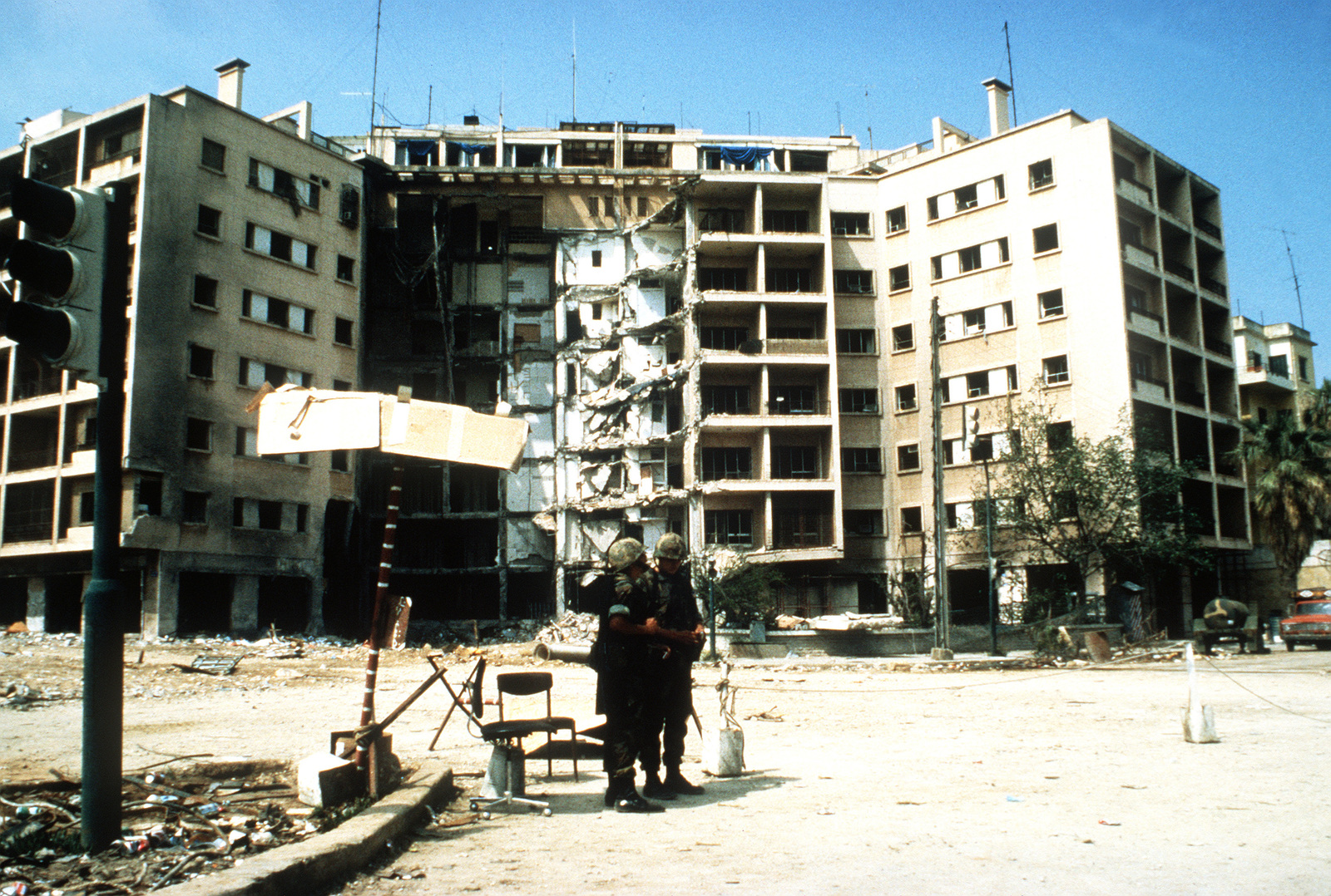 Two Marines stand in front of the U.S. Embassy which was destroyed by a terrorist bomb attack. The Marines are members of a multinational peacekeeping force