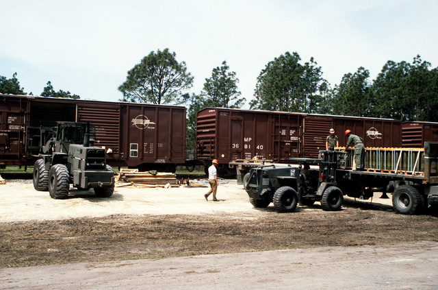 A Case M4K forklift truck is used to place pallets on a flatbed truck while an RT4000 forklift unloads a railroad car during LIFELINE Operations