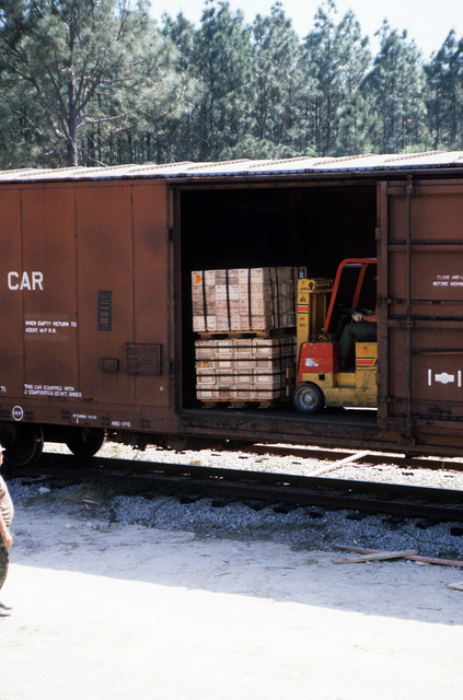 A commercial forklift is used to arange pallets inside a railroad car for transfer to flatbed trucks during LIFELINE Operations. The operations are being conducted by the 155th, 567th and 870th Transportation companies