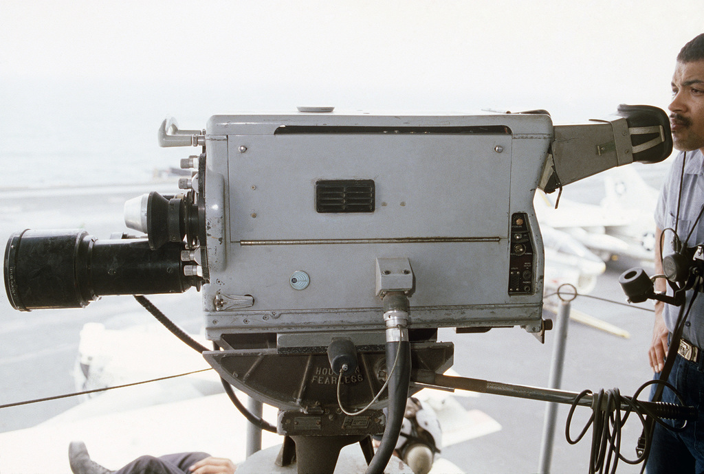 A crew member videotapes flight deck operations from a platform on the island of the nuclear-powered aircraft carrier USS DWIGHT D. EISENHOWER (CVN 69).  The camera is part of the pilot landing aid television system