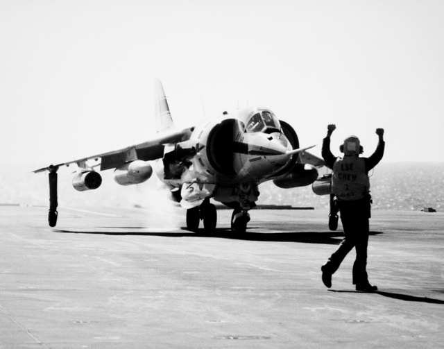 A flight deck crewman signals to the pilot of a AV-8C Harrier vertical/short takeoff and landing (V/STOL) aircraft. The Harrier, manufactured by McDonnell-Douglas, Inc., is undergoing a test and evaluation program