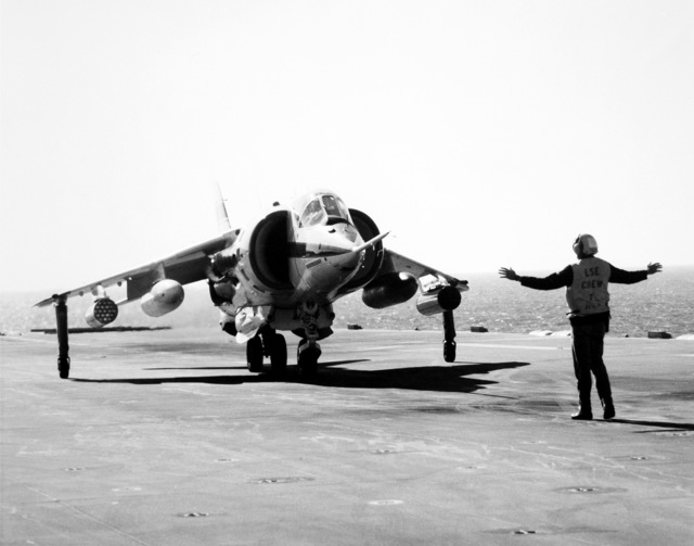 A flight deck crewman signals to the pilot of a Marine AV-8C Harrier vertical/short takeoff and landing (V/STOL) aircraft. The Harrier, manufactured by McDonnell-Douglas, Inc., is undergoing a test and evaluation program