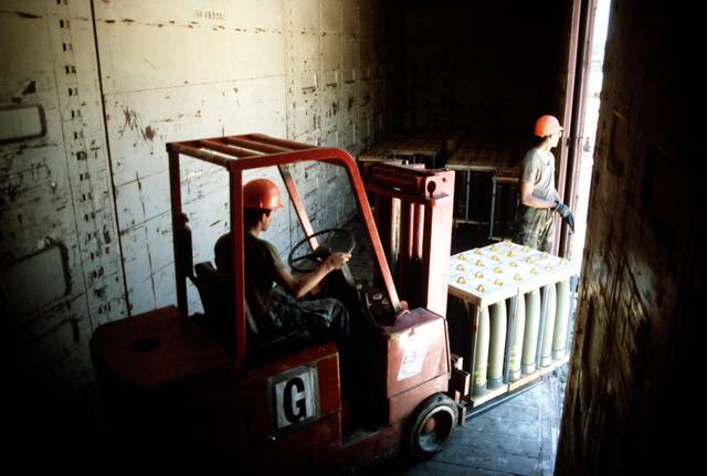 A forklift is used to position a pallet of 155 mm shells for unloading from a railroad car during LIFELINE Operations. The operations are being conducted by the 155th, 567th and 870th Transportation companies