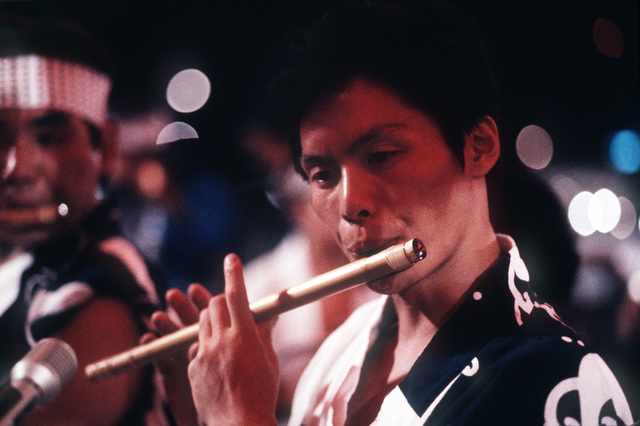 A Japanese flute player provides music for the annual community folk dancing ceremony known as Bon Odori. Bon Odori is one feature of the Obon services, which are similar to a Western-style All Soul's Day observance or Halloween. All Hands - May 1983
