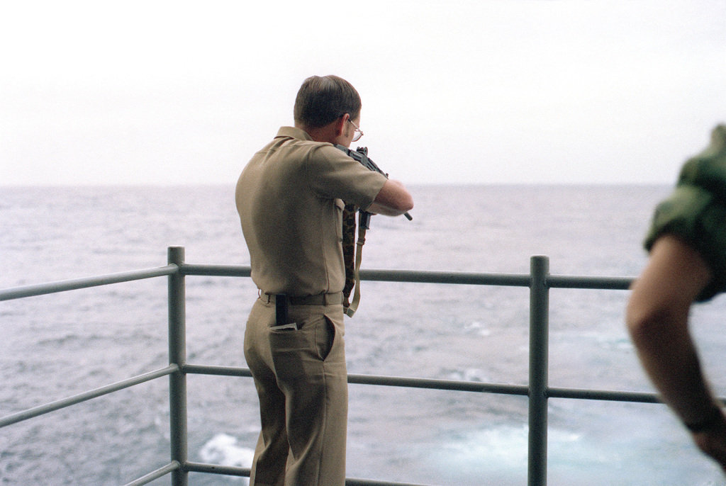A Navy officer fires an Uzi 9 mm submarine gun off the fantail of the aircraft carrier USS KITTY HAWK (CV 63) during a familiarization weapons firing exercise