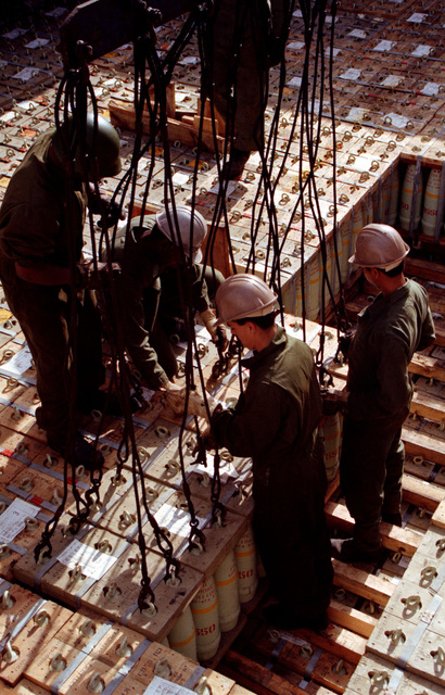A pallet of ammunition is attached to a crane to be offloaded from the cargo ship, during LIFELINE operations conducted by the 155th, 567th and 870th Transportation Companies