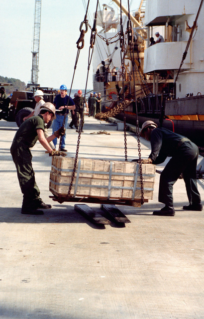 A pallet of ammunition is released from a crane after being offloaded from the cargo ship, during LIFELINE operations conducted by the 155th, 567th and 870th Transportation Companies