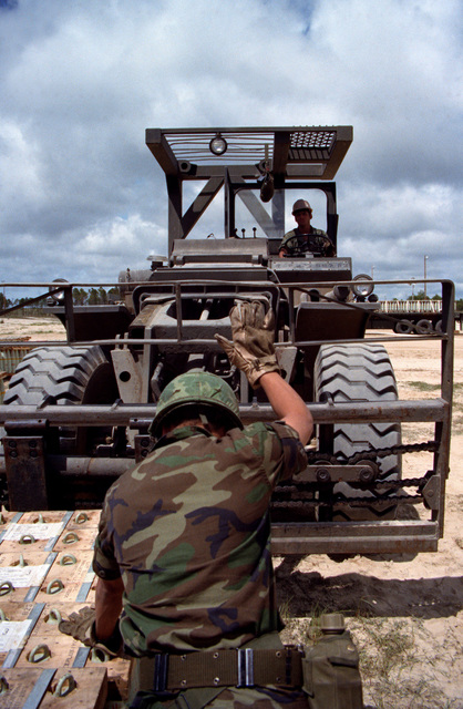 A soldier directs the operator of a five-ton forklift in picking up a pallet of 106 mm shells, during LIFELINE operations conducted by the 155th, 567th and 870th Transportation Companies