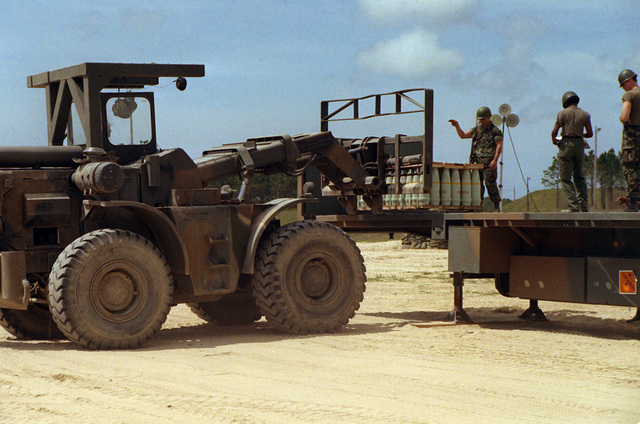 A soldier directs the operator of a five-ton forklift in picking up a pallet of 106mm shells, during Lifeline operations conducted by the 155th, 567th and 870th Transportation Companies