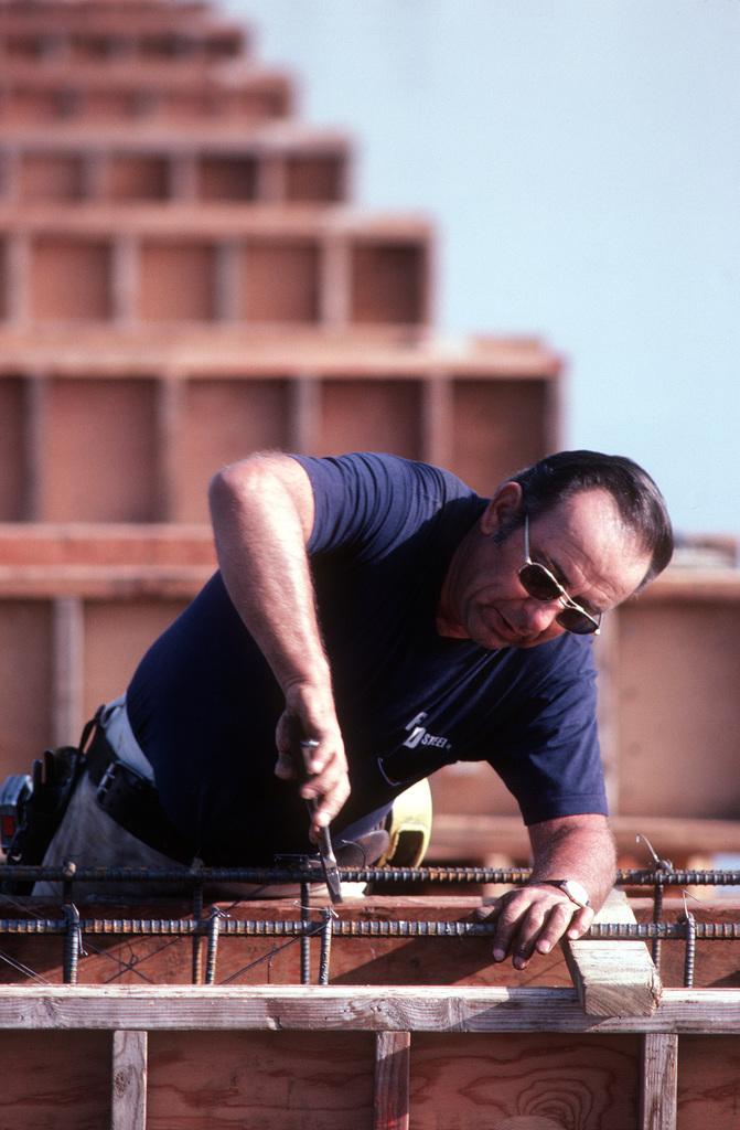 Alex Leon installs steel reinforcing rods in the framework of a ...