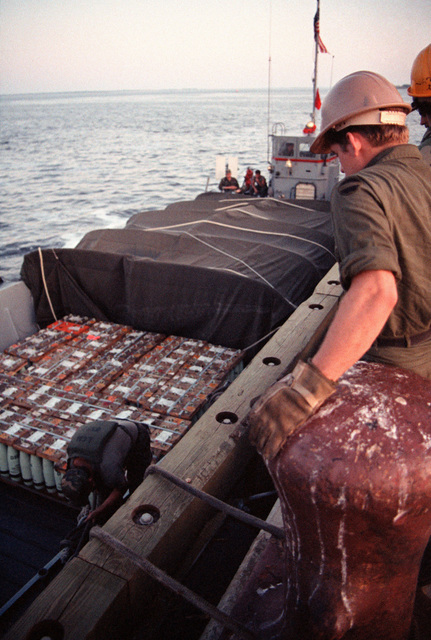 Ammunition is offloaded from a utility landing craft (LCU) during LIFELINE operations conducted by the 155th, 567th and 870th Transportation Companies
