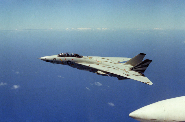 An air-to-air left side view of a Fighter Squadron 111 (VF-111) F-14A Tomcat aircraft, wings extended, assigned to the aircraft carrier USS KITTY HAWK (CV 63). The aircraft is armed with an AIM-9 Sidewinder air-to-air missile