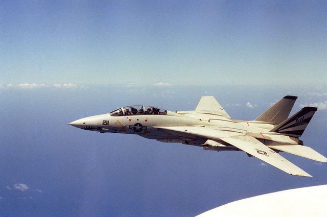 An air-to-air left side view of an F-14A Tomcat aircraft, wings swept back, from Fighter Squadron 111 (VF-111) assigned to the aircraft carrier USS KITTY HAWK (CV 63)