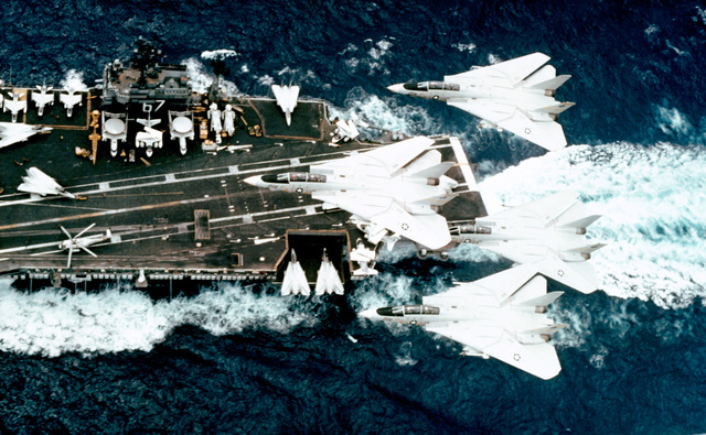 An air-to-air left side view of four F-14 Tomcat aircraft flying over the aircraft carrier USS JOHN F. KENNEDY (CV-67)