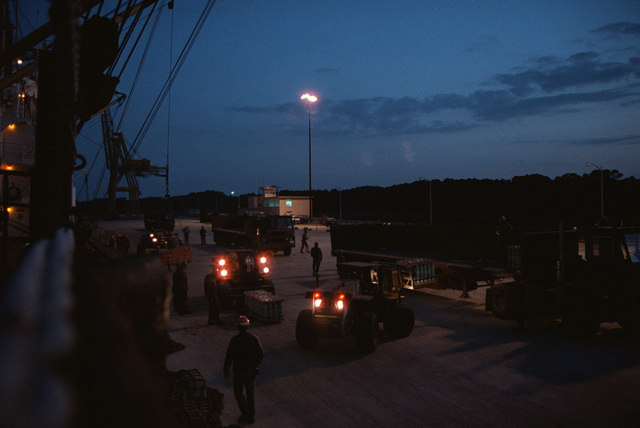 An overall nighttime view as forklifts are used to load pallets onto trucks, during LIFELINE operations conducted by the 155th, 567th and 870th Transportation Companies