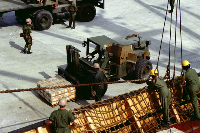 An RT-4000 forklift is used to pick up a pallet of 20 mm shells after they were offloaded from a cargo ship, during LIFELINE operations conducted by the 155th, 567th and 870th Transportation Companies