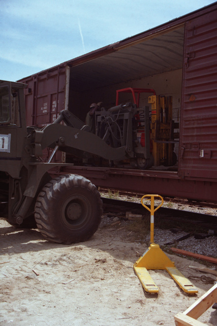 An RT-4000 forklift is used to pick up a pallet of ammunition from a commercial 4000 forklift on a rail car, during Lifeline operations conducted by the 155th, 567th and 870th Transportation Companies