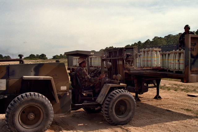 An RT-4000 forklift is used to unload ammunition from a flatbed truck during LIFELINE operations conducted by the 155th, 567th and 870th Transportation Companies