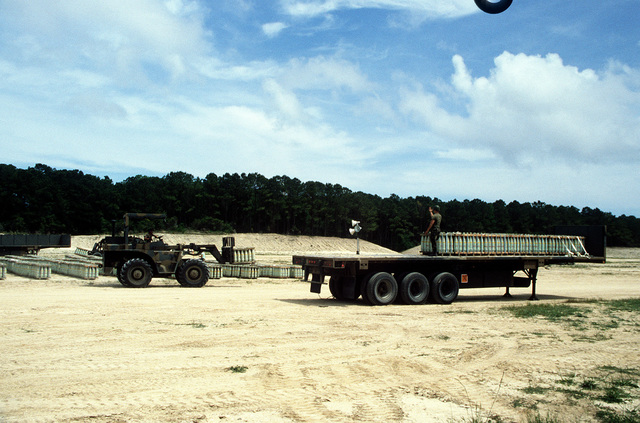 An RT4000 forklift is used to unload pallets of shells from an M872 trailer during LIFELINE Operations. The operations are being conducted by the 155th, 567th and 870th Transportation companies