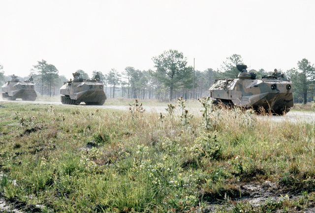 Armored personnel carriers from the 2nd Amtrac Battalion en route to Combat Town during Exercise Solid Shield '83