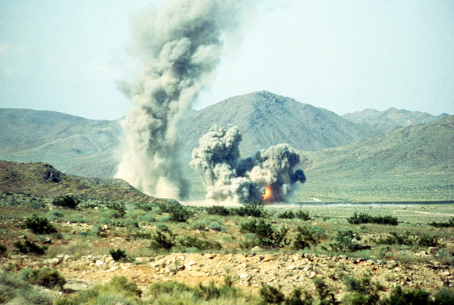 Bombs explode in the desert following an air strike during Combined Arms exercises Five and Six