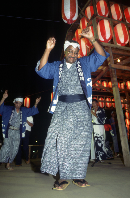 Captain Otis M. Brooks, commanding officer of NAF Atsugi, wears a traditional costume while participating in the annual community folk dancing ceremony known as Bon Odori. The dancing is a feature of the Obon services, which are similar to a Western-style All Soul's Day observance or Halloween. All Hands - May 1983