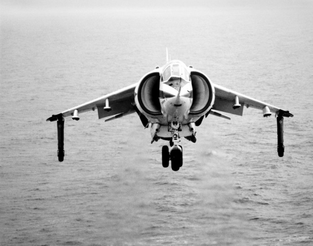 Front view of an AV-8C Harrier vertical/short takeoff and landing (V/STOL) aircraft coming in for a landing aboard an aircraft carrier. The Harrier, manufactured by McDonnell-Douglas, Inc., is undergoing a test and evaluation program
