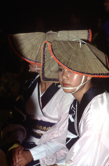 Japanese dancers watch activities taking place during the annual community folk dancing ceremony known as Bon Odori. Bon Odori is one feature of the Obon services, which are similar to a Western-style All Soul's Day or Halloween. All Hands - May 1983
