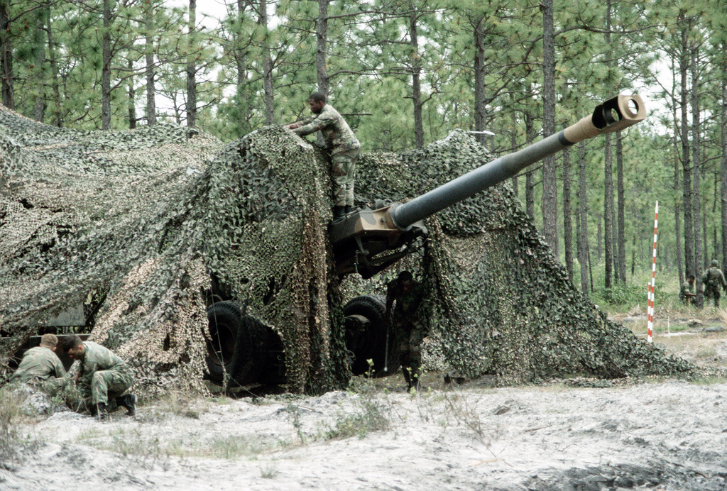 Members of the 10th Marine Regiment camouflage an XM-198 155mm howitzer at Tactical Landing Zone Cardinal during Exercise Solid Shield '83