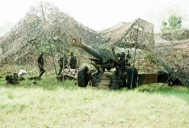 Members of the 10th Marine Regiment examine an XM-198 155mm howitzer under camouflage during Exercise Solid Shield '83 at Tactical Landing Zone Eagle