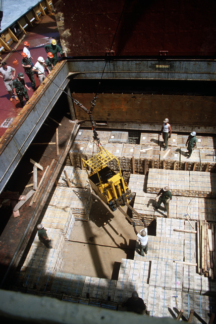 Members of the 155th Transportation Company lower a commercial forklift into the hold of the chartered Military Sealift Command cargo ship BUILDER (T-AK 2031) during LIFELINE Operations