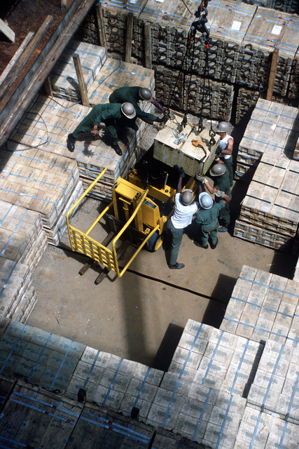 Members of the 155th Transportation Company lower the battery into a commercial forklift in the hold of the chartered Military Sealift Command cargo ship BUILDER (T-AK 2031) during LIFELINE Operations