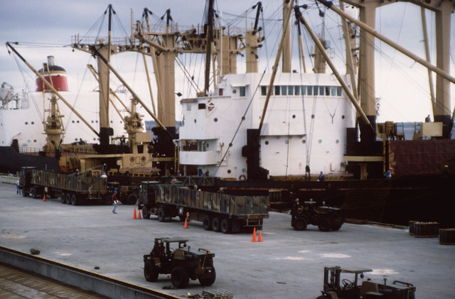 Members of the 155th Transportation Company prepare to unload cargo from the chartered Military Sealift Command cargo ship Builder (AK) onto M872 trailers during LIFELINE Operations