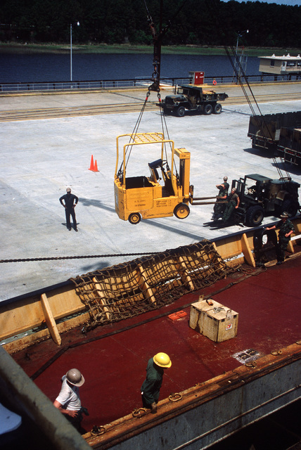 Members of the 155th Transportation Company transfer a commercial forklift from the dock to the hold of the chartered Military Sealift Command cargo ship BUILDER (T-AK 2031) during LIFELINE Operations