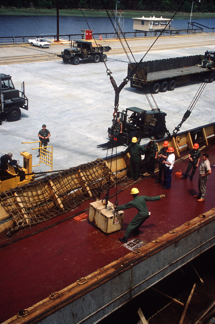 Members of the 155th Transportation Company transfer the battery for a commercial forklift from the main deck to the hold of the chartered Military Sealift Command cargo ship BUILDER (T-AK 2031) during LIFELINE Operations