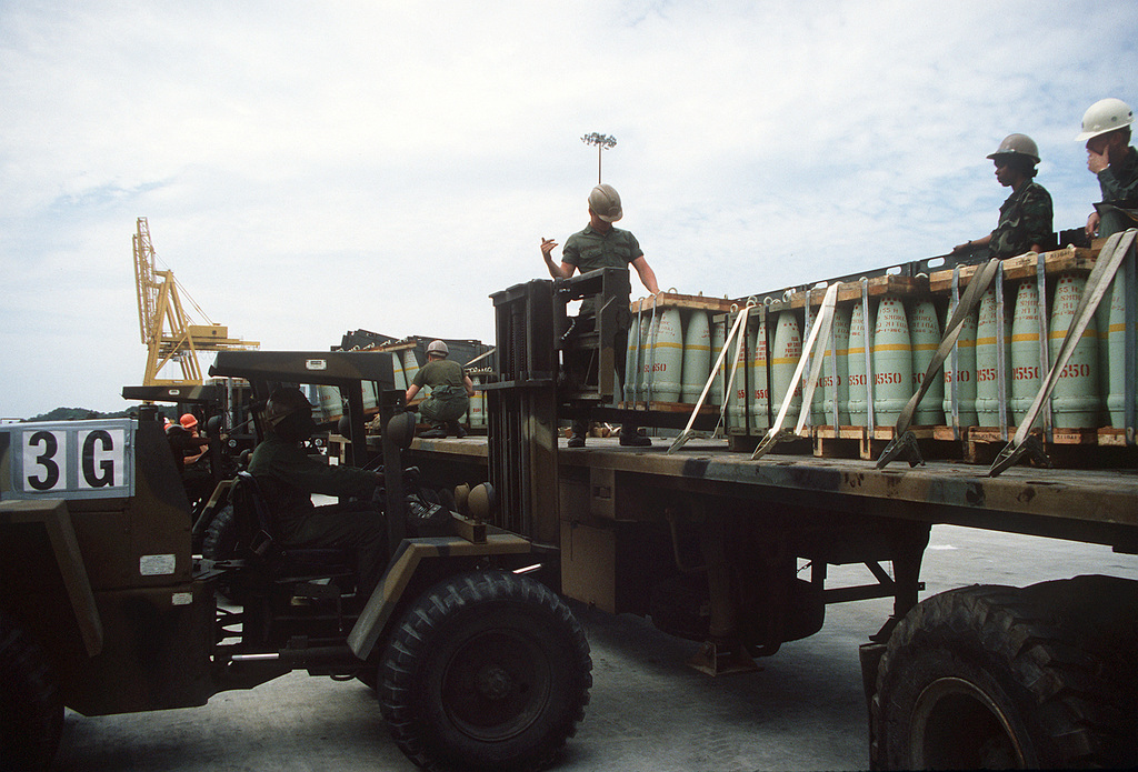 Members of the 155th Transportation Company use a Case M4K rough terrain forklift truck to load pallets of 155mm shells onto trucks during Lifeline Operations