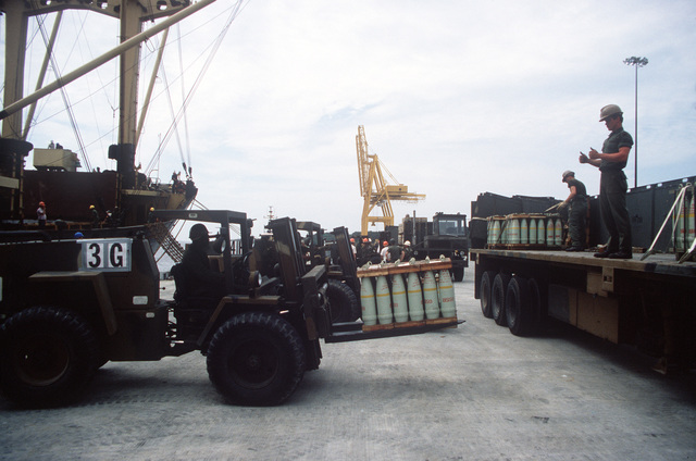 Members of the 155th Transportation Company use a Case M4K rough terrain forklift truck to load pallets of 155 mm shells onto trucks during LIFELINE Operations