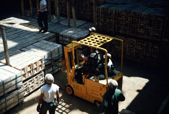 Members of the 155th Transportation Company use a forklift to position pallets for unloading from the chartered Military Sealift Command cargo ship BUILDER (T-AK 2031) during LIFELINE Operations