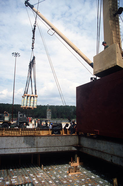 Members of the 155th Transportation Company use a winch to unload pallets of 155 mm shells from the chartered Military Sealift Command cargo ship BUILDER (T-AK 2031) during LIFELINE Operations