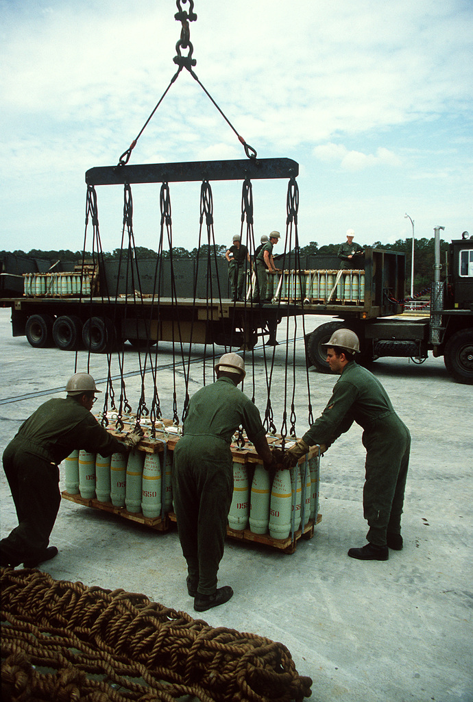 Members of the 155th Transportation Company uses a winch to move pallets of 155mm shells during Lifeline Operations
